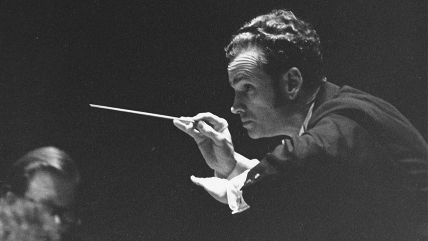 A close-up of Louis Lane conducting a concert at Severance Hall. He is bent forward slightly and gesturing to the players to play softly.