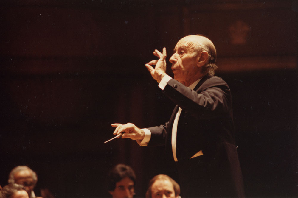 Leinsdorf guest conducting the Orchestra. He is making a gesture with his left thumb and forefinger to emphasize the tapering of a musical phrase.