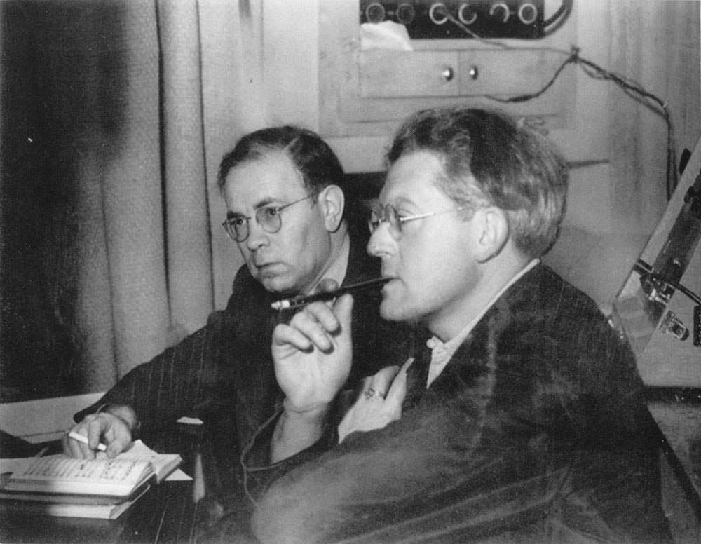 Rodzinski is seated and holding a cigarette holder in his mouth while he contemplates the playback of a prospective recording by The Cleveland Orchestra. A small score is open in front of him.