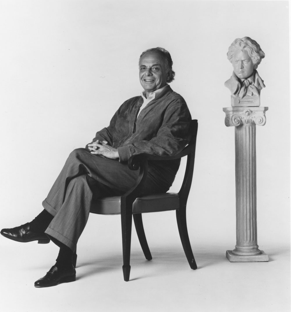 Maazel is seated and smiling at the camera while behind him, to the left, is a bust of Beethoven.