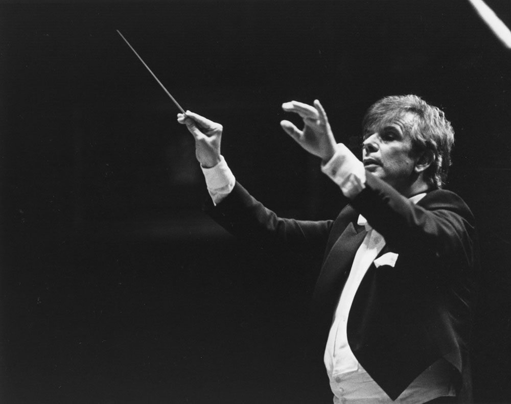 Photograph focused closely on Christoph von Dohnányi. He is conducting, and is in the middle of a cue.