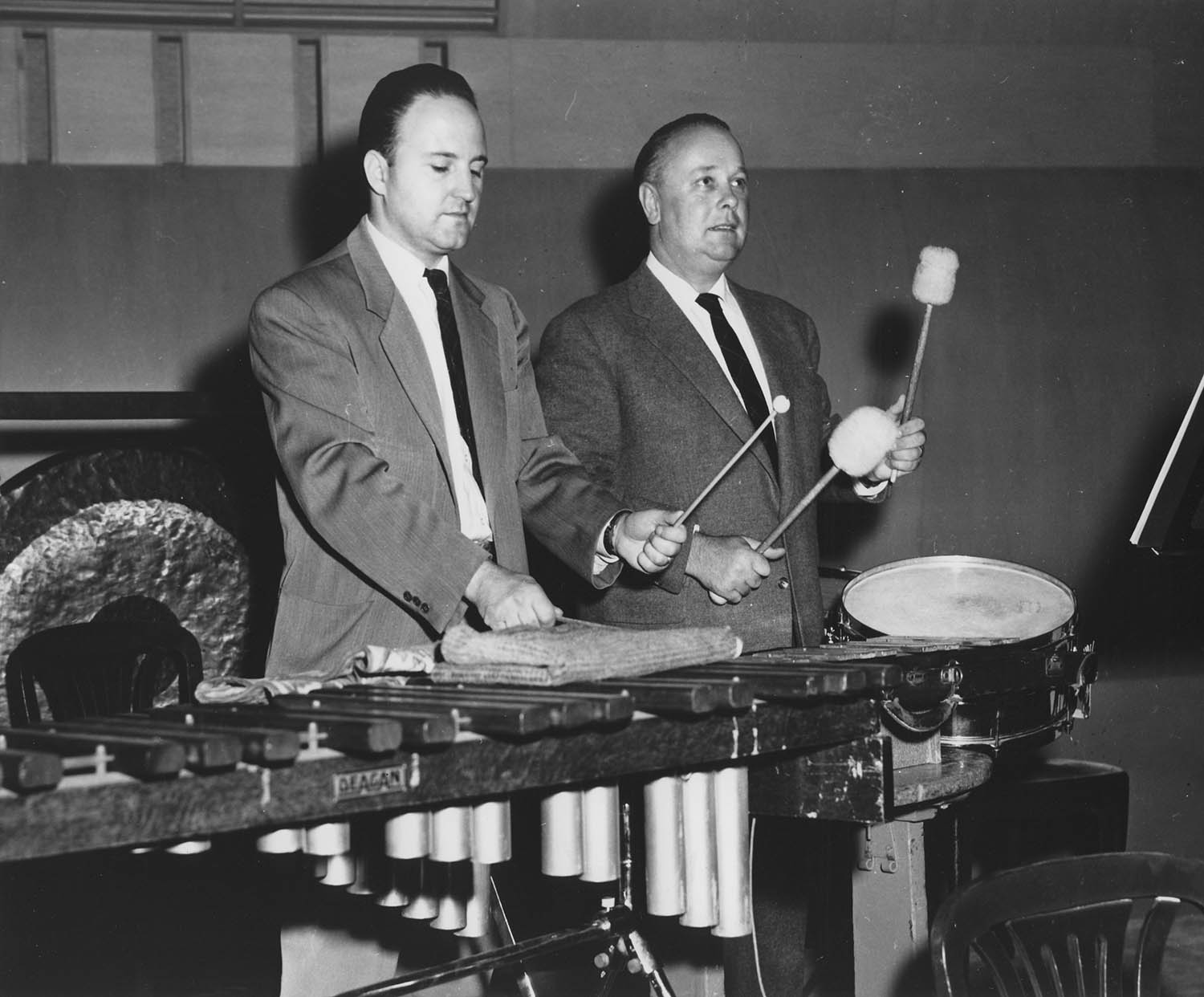 Program annotator Klaus George Roy (Left) and acoustical consultant Heinrich Keilholz (Right) conduct tests on reverberation times with percussion instruments on the renovated Severance Hall stage. Unknown photographer, 1958.