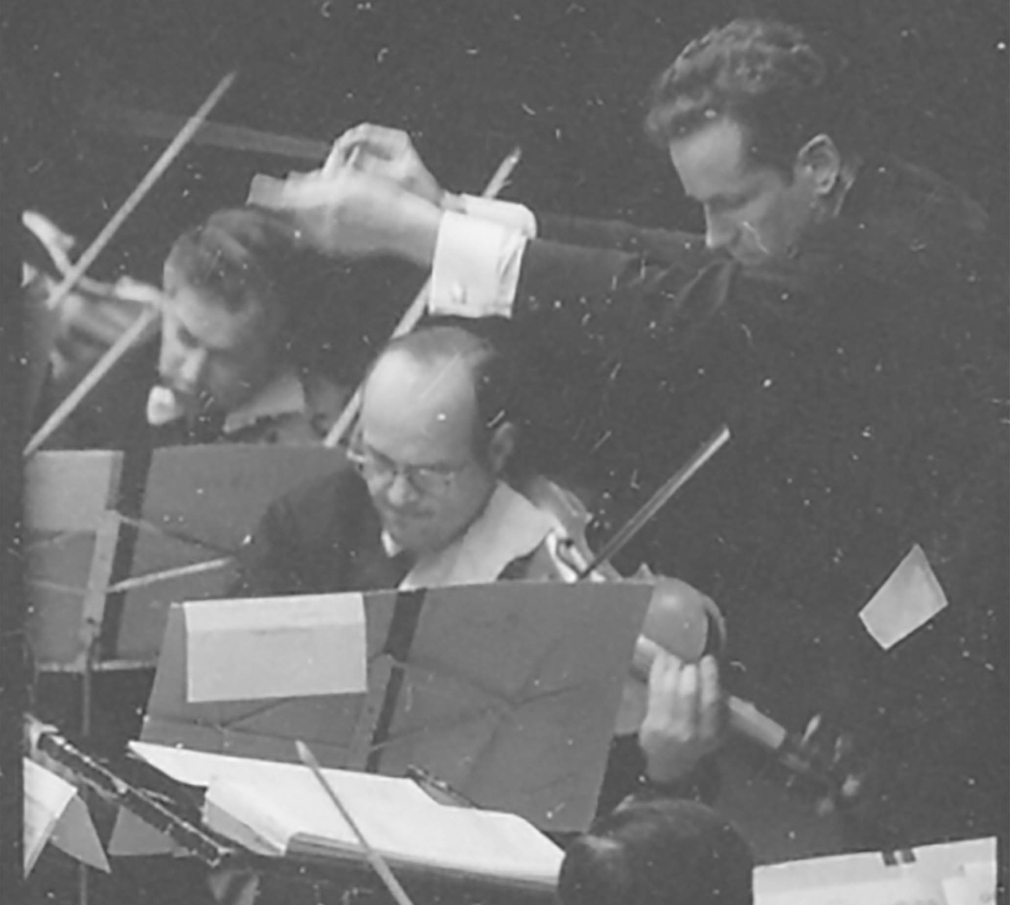 A youthful Louis Lane conducts the Orchestra. Everyone wears a serious, intense expression.t