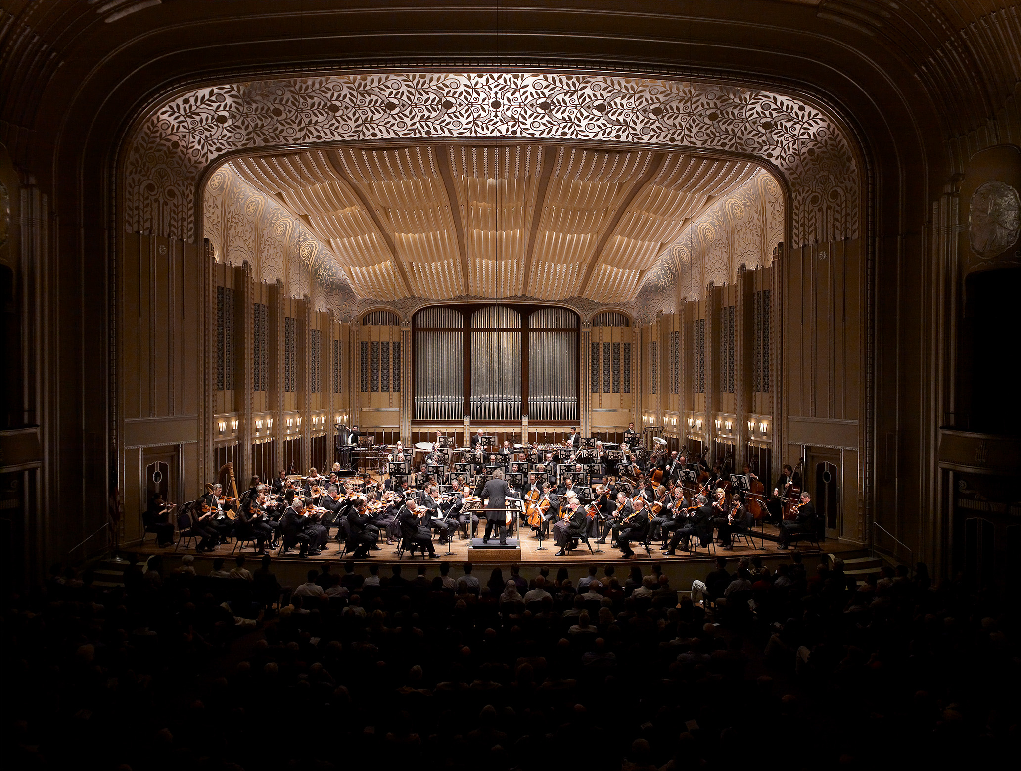 The Cleveland Orchestra, conducted by Franz Welser-Möst, is performing in Severance Hall. The photo shows the Orchestra and Franz animatedly performing and conducting, respectively.