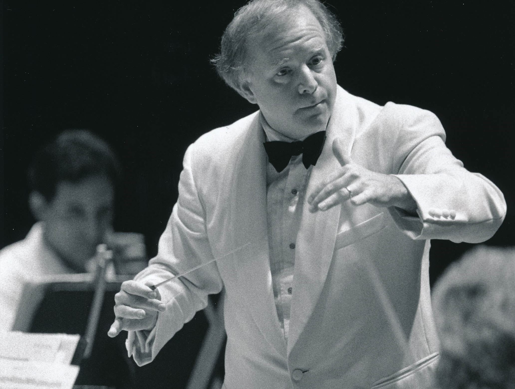 Leonard Slatkin conducting the Orchestra at Blossom Music Center. Slatkin and the Orchestra are dressed in white, which is formal dress for Blossom performances.