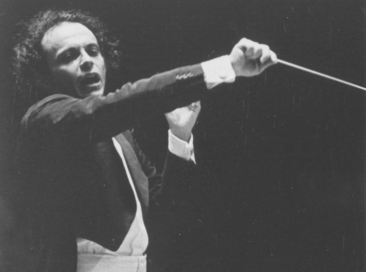 Maazel is conducting the Orchestra. His hair looks wild, and he is conducting aggressively.
