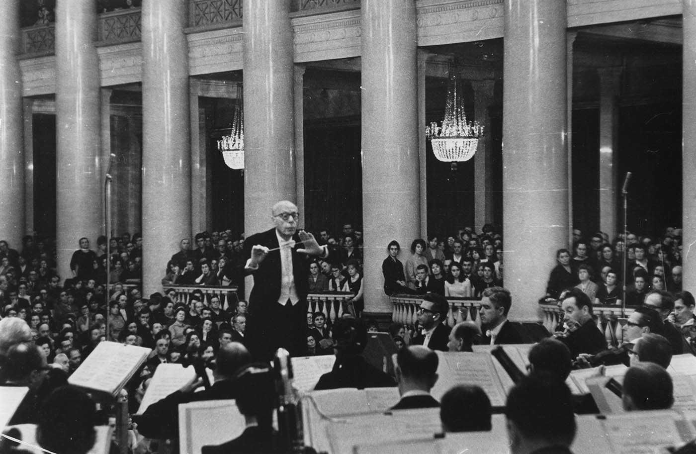 Szell is conducting the Orchestra. A large, attentive audience is seated behind them. Prominent chandeliers hang above the audience.
