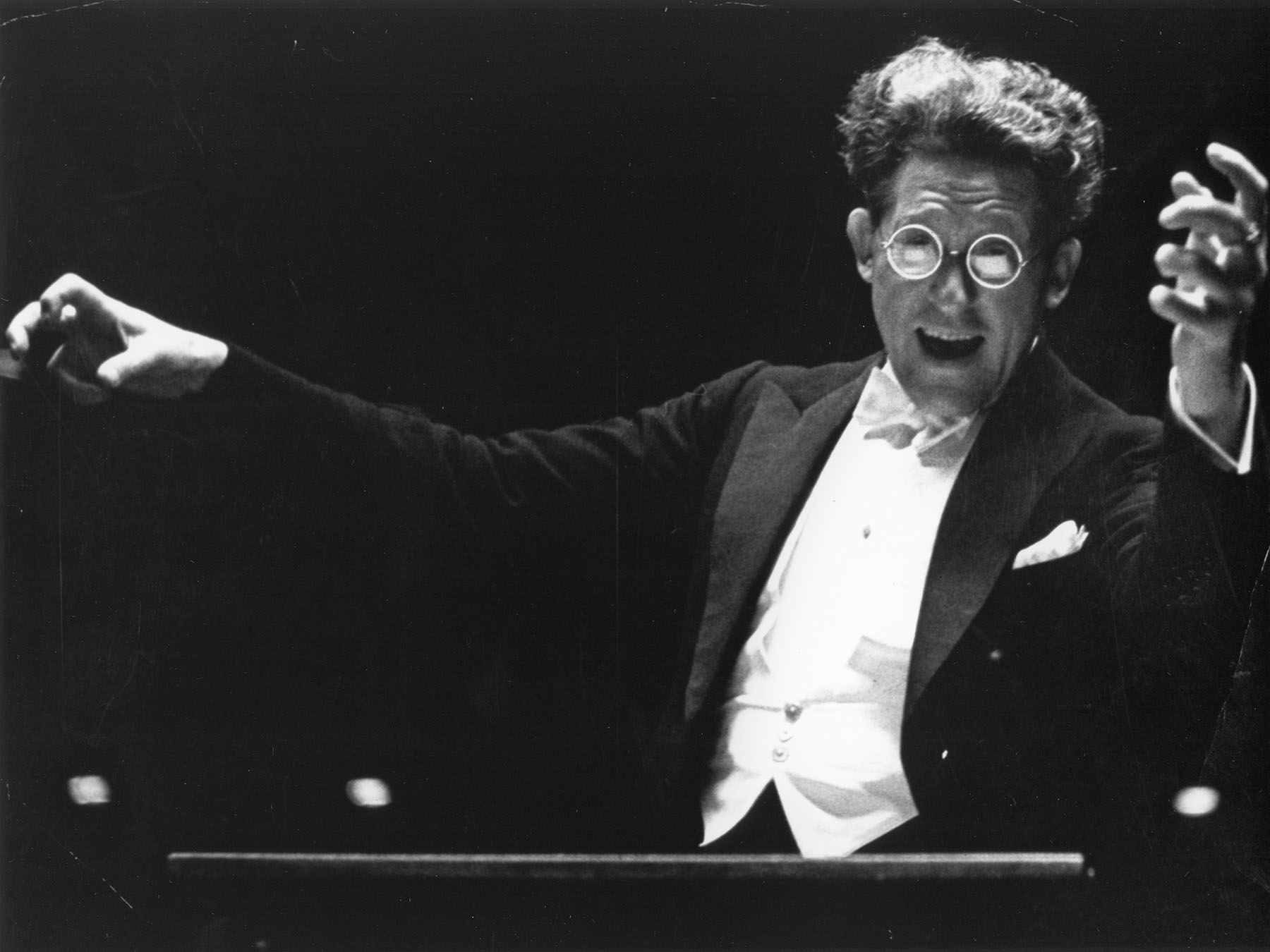Artur Rodzinski conducting the Orchestra. He is facing the viewer, has a huge, excited smile on his face, and is wearing large glasses.